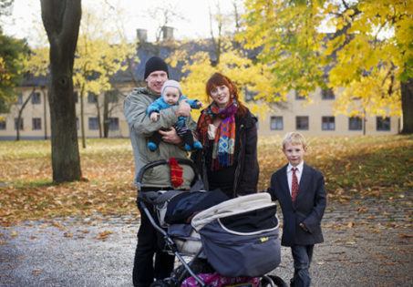Familjeporträtt, pappa, mamma och två barn i en park på hösten.