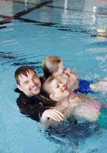 En man i simbassäng med två barn.