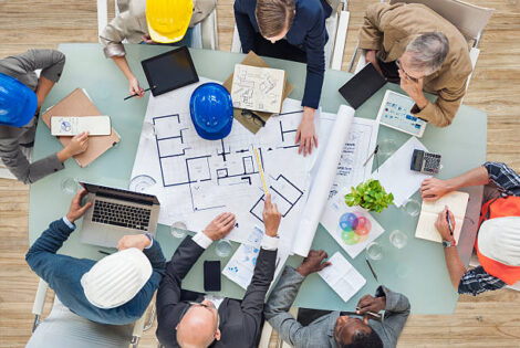 Personer sitter runt ett bord med en ritning