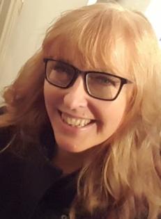 Leende kvinna med långt blont hår och glasögona
